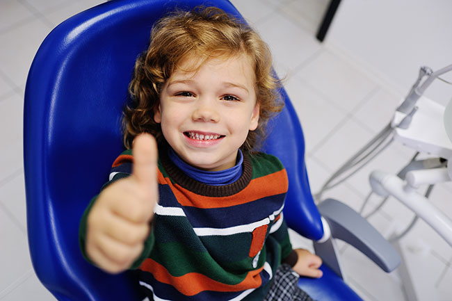 happy pediatric dental patient in office exam chair