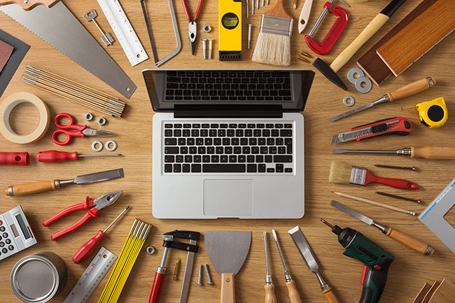 laptop surrounded by many tools